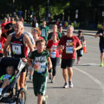 A father runs with his two children during the 5K race